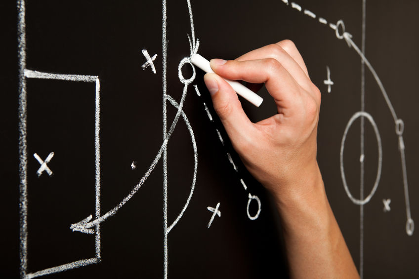 Hand drawing a soccer game tactics with white chalk on blackboard.